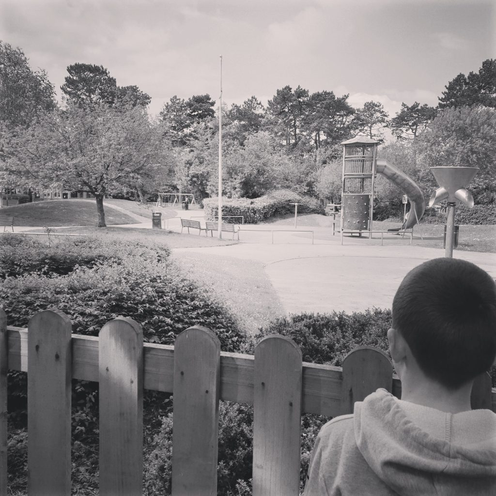 LHL_2020_004: Black and white photographic depicting the back of Freddie's head, he is looking at the closed and empty play area in Bruntwood Park, Stockport, on 2nd May 2020.