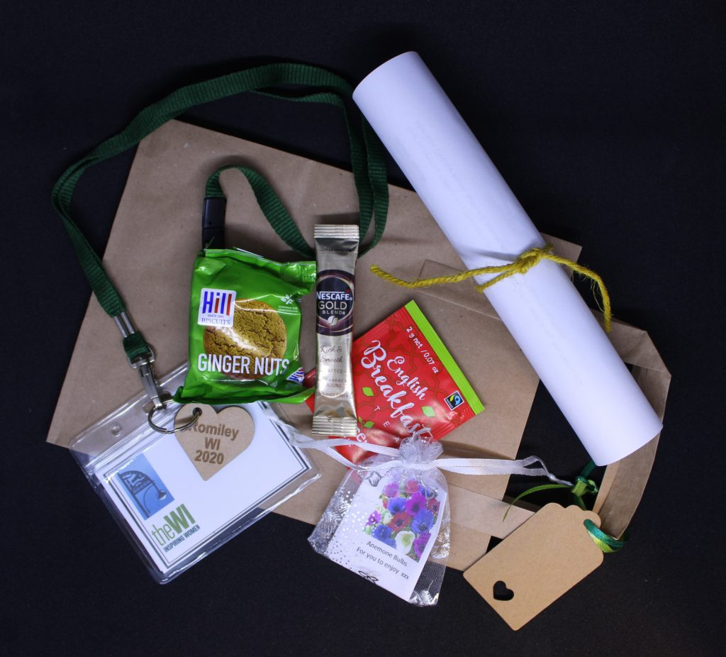 LHL_2020_007b: a photograph of a number of items lay on a brown paper bag. They are a packet of ginger nut biscuits, a sachet of coffee, an English Breakfast tea bag, a rolled up piece of paper tied with yellow string, a mesh bag containing a plant bulb, and a green lanyard attached to a plastic name tag.