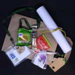 LHL_2020_007b: a photograph of a number of items lay on a brown paper bag. They are a packet of ginger nut biscuits, a sachet of coffee, an English Breakfast tea bag, a rolled up piece of paper tied with yellow string, a mesh bag containing a plant bulb, and a green lanyard attached to a plastic name tag. Thumbnail