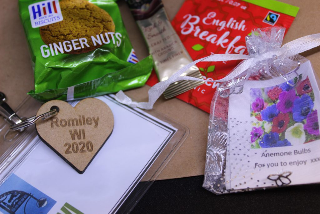LHL_2020_007c: a close up photograph of the items lay on a brown paper bag - a packet of ginger nut biscuits, a sachet of coffee, an English Breakfast tea bag, a mesh bag containing a plant bulb, and the name tag which has a wooden heart-shaped keyring charm, stamped with 'Romiley WI 2020'.