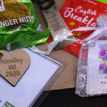 LHL_2020_007c: a close up photograph of the items lay on a brown paper bag - a packet of ginger nut biscuits, a sachet of coffee, an English Breakfast tea bag, a mesh bag containing a plant bulb, and the name tag which has a wooden heart-shaped keyring charm, stamped with 'Romiley WI 2020'. Thumbnail