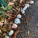 LHL_2020_008a: photograph showing a row of rocks and pebbles on a pavement with crisp brown leaves behind them.  The rocks and pebbles have been painted with images and messages. Thumbnail