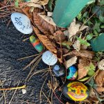 LHL_2020_008b: photograph showing a close-up of painted rocks on a pavement. Some of the decorations include the words '2nd Cheadle Scouts 2020', 'Be Kind', and the Manchester United logo. Thumbnail
