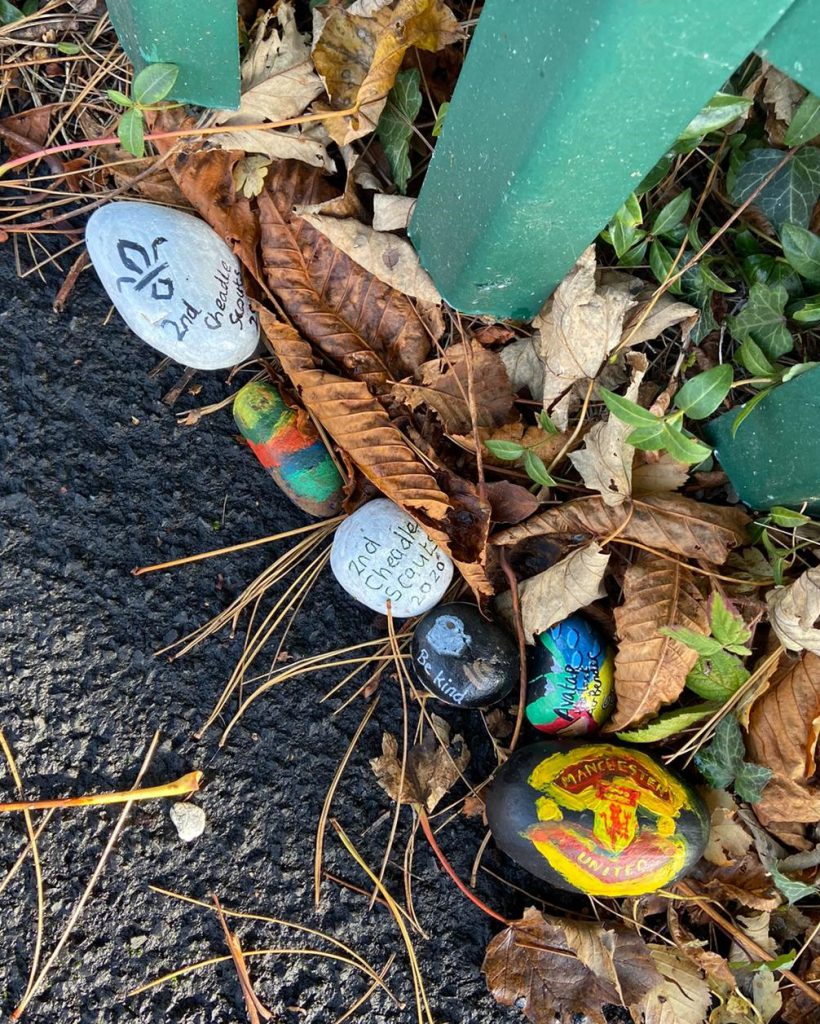 LHL_2020_008b: photograph showing a close-up of painted rocks on a pavement. Some of the decorations include the words '2nd Cheadle Scouts 2020', 'Be Kind', and the Manchester United logo.