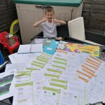 LHL_2020_009a: Photograph showing 8 year old Alex stood at a garden table which is covered by work sheets. Thumbnail