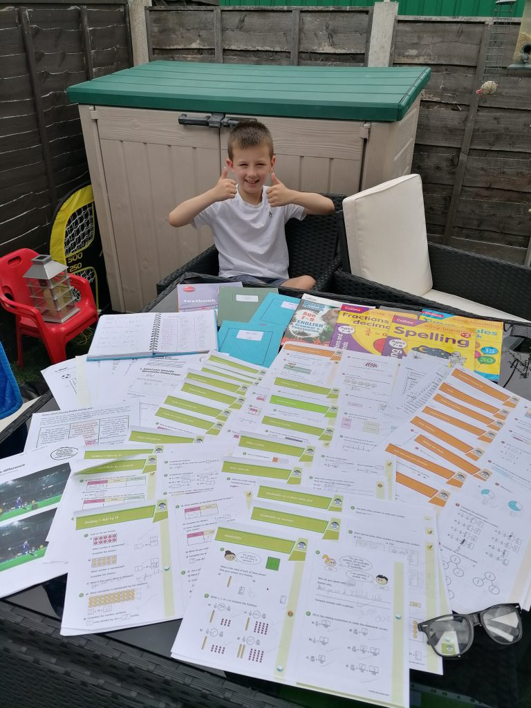 LHL_2020_009a: Photograph showing 8 year old Alex stood at a garden table which is covered by work sheets.