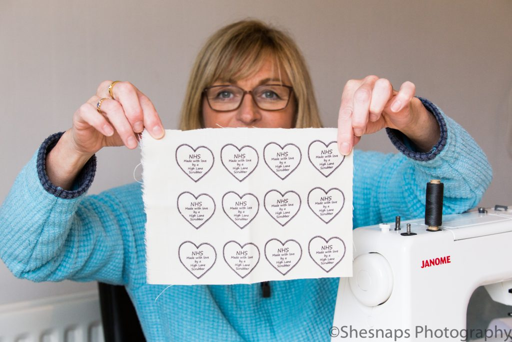 LHL_2020_014a – A 'High Lane Scrubber' holds up a piece of fabric which has the labels to be sewn into hand made scrubs for NHS workers.  Many people across the UK began sewing scrubs at home and donating them to hospitals due to a nationwide shortage of the plain clothes worn by the medical professionals.  Due to fast spread of Covid-19, the personal protective equipment NHS staff were wearing needed to be changed more frequently than would be normally, and as a result these were in high demand. Volunteers started sewing from donated material and fabric, to create scrubs sets, bags to transport dirty scrubs in for washing, caps, masks and even 'ear savers' to alleviate pain when wearing face masks.