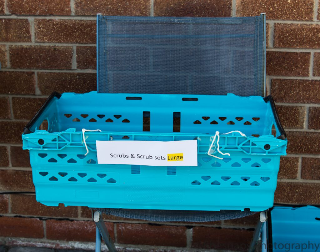 LHL_2020_014b - High Lane Scrubber – A blue basket containing handmade scrubs for hospital workers sits on a chair in the shade.