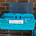 LHL_2020_014b - High Lane Scrubber – A blue basket containing handmade scrubs for hospital workers sits on a chair in the shade. Thumbnail