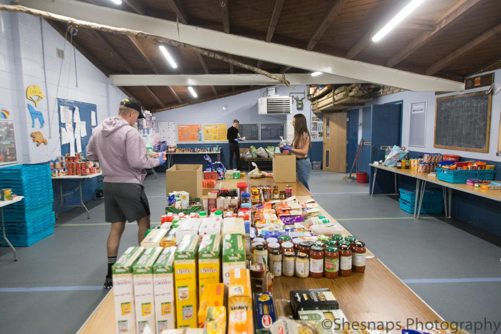 LHL_2020_014d – Food provisions inside the 1st High Lane Scouts hut. Many people who were shielding and could not leave the house to go shopping; or those who could not work and were facing financial hardship were helped out by local food banks and shopping hubs such as this. Food parcels created from donations were delivered to local residents safely and from a distance by volunteers.