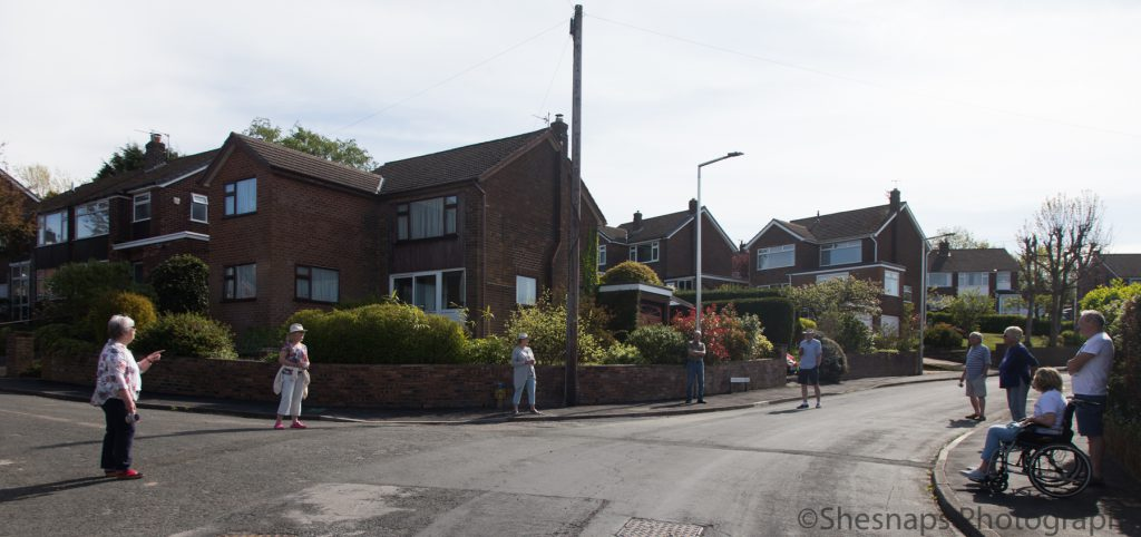 LHL_2020_014f – The residents from a street in High Lane stand socially distanced on the pavement on a sunny evening.