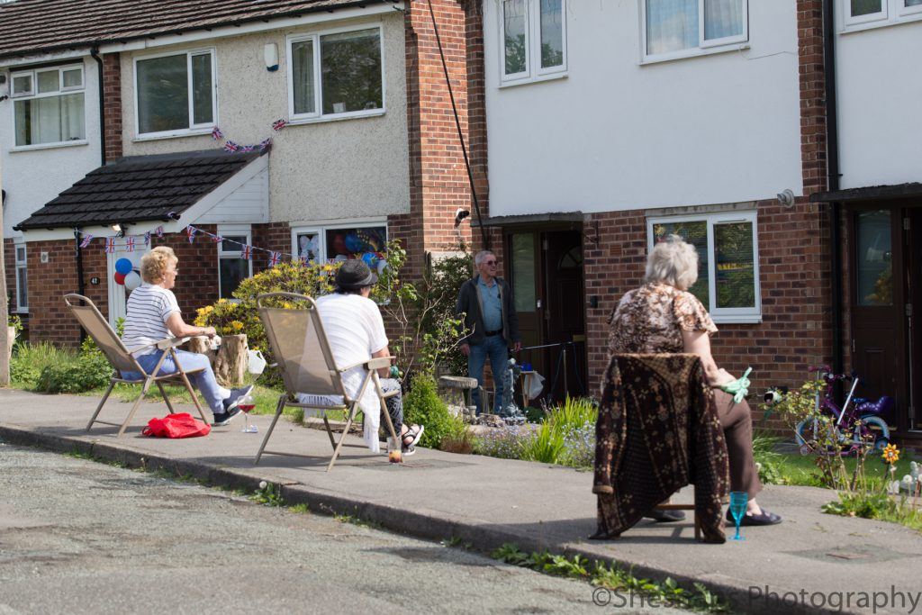 LHL_2020_014h – VE Day in High Lane. The 75th anniversary of VE day happened during the lockdown in the UK.  Many people decorated their houses and sat outside for socially distanced celebrations. Here three residents from a street in High Lane sit on garden chairs. The house on the left is adorned with Union Flag bunting, and red, white and blue balloons on the front door.