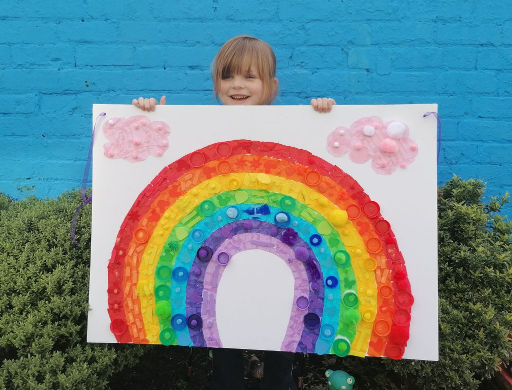 LHL_2020_021a: Photograph of Isla holding a large rainbow sign which she made.