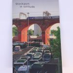STOPM_2020_418a: A booklet; the front cover of the zine entitled 'Stockport in Solitude' by Jake Bowden. It features a photograph of a train going over the Stockport Viaduct, with Stockport bus station below, taken by Jake in 2020.  Thumbnail