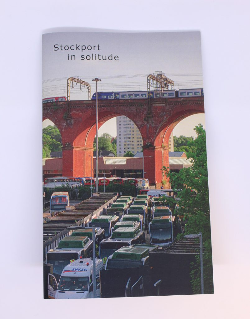STOPM_2020_418a: A booklet; the front cover of the zine entitled 'Stockport in Solitude' by Jake Bowden. It features a photograph of a train going over the Stockport Viaduct, with Stockport bus station below, taken by Jake in 2020.