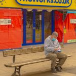 STOPM_2020_418d: Photograph of a masked person sat on a bench, outside TheWorks shop in Stockport, taken by Jake Bowden. Thumbnail