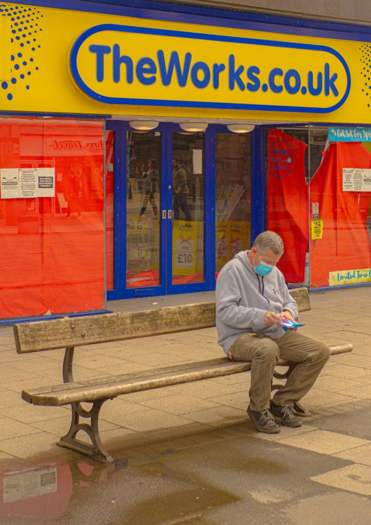 STOPM_2020_418d: Photograph of a masked person sat on a bench, outside TheWorks shop in Stockport, taken by Jake Bowden.