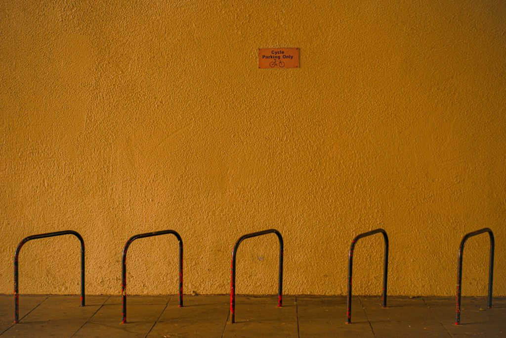 STOPM_2020_418e: Photograph of a mustard yellow wall, with a bike rack in the foreground, taken by Jake Bowden.
