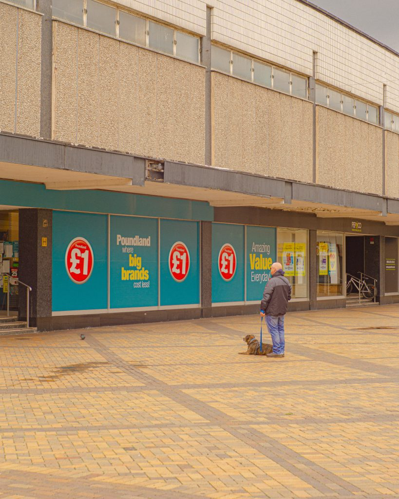 TOPM_2020_418g: photograph of a person and a dog in Merseyway, looking at Poundland, taken by Jake Bowden.