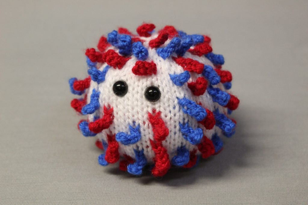 STOPM_2020_452a: Image of knitted toy or souvenir of an anthropomorphic coronavirus; white spherical shape with blue and red 'spikes' to mimic the structure of the coronavirus particle. Two black plastic domed beads/buttons have been added as 'eyes'. The coronavirus was knitted in red, white and blue to commemorate the 75th anniversary of VE (Victory in Europe) Day which was celebrated on 8th May 2020. Knitted by Linda Cornes Parker, who is a part of the group Knitting Friends in the Park.; knitted toy or souvenir of an anthropomorphic coronavirus; white with multicoloured speckles spherical shape with 'spikes' to mimic the structure of the coronavirus particle. Two black plastic domed beads/buttons have been added as 'eyes'.  A wooden cocktail stick and a wooden parallelogram have been cello taped and stuck into the ball as a sign which has been written on in black pen 'WASH YOUR HANDS'. Knitted by Linda Cornes Parker, who is a part of the group Knitting Friends in the Park.