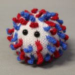 STOPM_2020_452a: Image of knitted toy or souvenir of an anthropomorphic coronavirus; white spherical shape with blue and red 'spikes' to mimic the structure of the coronavirus particle. Two black plastic domed beads/buttons have been added as 'eyes'. The coronavirus was knitted in red, white and blue to commemorate the 75th anniversary of VE (Victory in Europe) Day which was celebrated on 8th May 2020. Knitted by Linda Cornes Parker, who is a part of the group Knitting Friends in the Park.; knitted toy or souvenir of an anthropomorphic coronavirus; white with multicoloured speckles spherical shape with 'spikes' to mimic the structure of the coronavirus particle. Two black plastic domed beads/buttons have been added as 'eyes'.  A wooden cocktail stick and a wooden parallelogram have been cello taped and stuck into the ball as a sign which has been written on in black pen 'WASH YOUR HANDS'. Knitted by Linda Cornes Parker, who is a part of the group Knitting Friends in the Park. Thumbnail