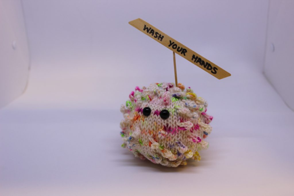 STOPM_2020_453a: knitted toy or souvenir of an anthropomorphic coronavirus; white with multicoloured speckles spherical shape with 'spikes' to mimic the structure of the coronavirus particle. Two black plastic domed beads/buttons have been added as 'eyes'.  A wooden cocktail stick and a wooden parallelogram have been cello taped and stuck into the ball as a sign which has been written on in black pen 'WASH YOUR HANDS'. Knitted by Linda Cornes Parker, who is a part of the group Knitting Friends in the Park.