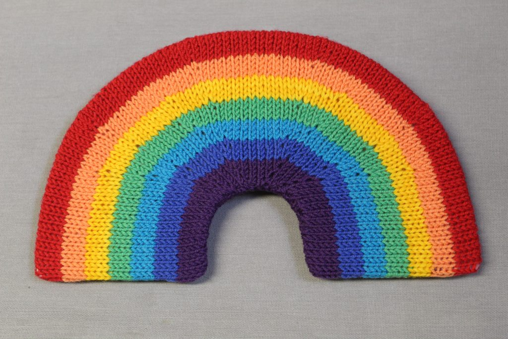 STOPM_2020_454a: knitted toy or souvenir of a rainbow; arch-shaped piece of flexible plastic, covered with a knitted rainbow in the colours of red, orange, yellow, green, turquoise, blue, and purple. Knitted by Linda Cornes Parker, who is a part of the group Knitting Friends in the Park.