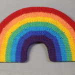 STOPM_2020_454a: knitted toy or souvenir of a rainbow; arch-shaped piece of flexible plastic, covered with a knitted rainbow in the colours of red, orange, yellow, green, turquoise, blue, and purple. Knitted by Linda Cornes Parker, who is a part of the group Knitting Friends in the Park. Thumbnail