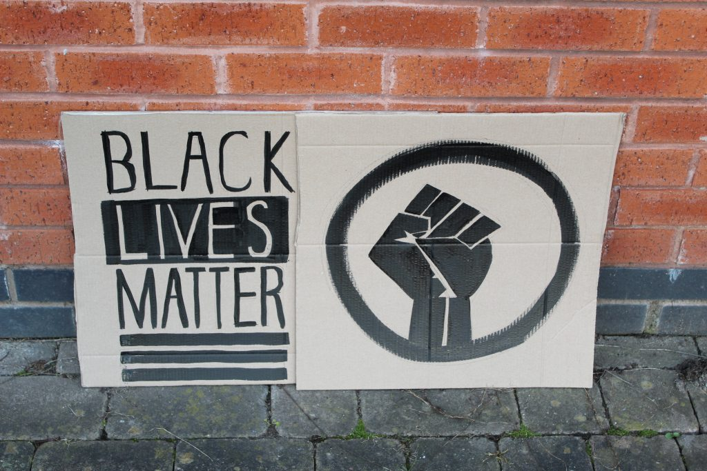 STOPM_2020_455_456a: Photo of two home made placards, stood in front of a red brick building.  The signs have been made from sections of a cardboard box. One sign has been drawn and painted with the words 'BLACK LIVES MATTER', and the other has been painted with the symbol of a black raised fist in a circle. The clenched fist has become synonymous with the Black Lives Matter movement but has a long history.