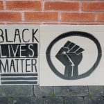 STOPM_2020_455_456a: Photo of two home made placards, stood in front of a red brick building.  The signs have been made from sections of a cardboard box. One sign has been drawn and painted with the words 'BLACK LIVES MATTER', and the other has been painted with the symbol of a black raised fist in a circle. The clenched fist has become synonymous with the Black Lives Matter movement but has a long history. Thumbnail