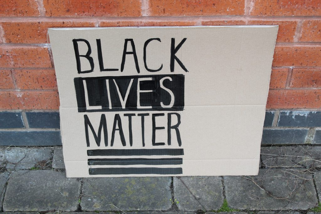 STOPM_2020_455a: Photo of a home made placard, stood in front of a red brick building. The sign has been made from a section of a cardboard box.  The sign has been drawn and painted with the words 'BLACK LIVES MATTER' in black paint.