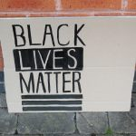 STOPM_2020_455a: Photo of a home made placard, stood in front of a red brick building. The sign has been made from a section of a cardboard box.  The sign has been drawn and painted with the words 'BLACK LIVES MATTER' in black paint.  Thumbnail