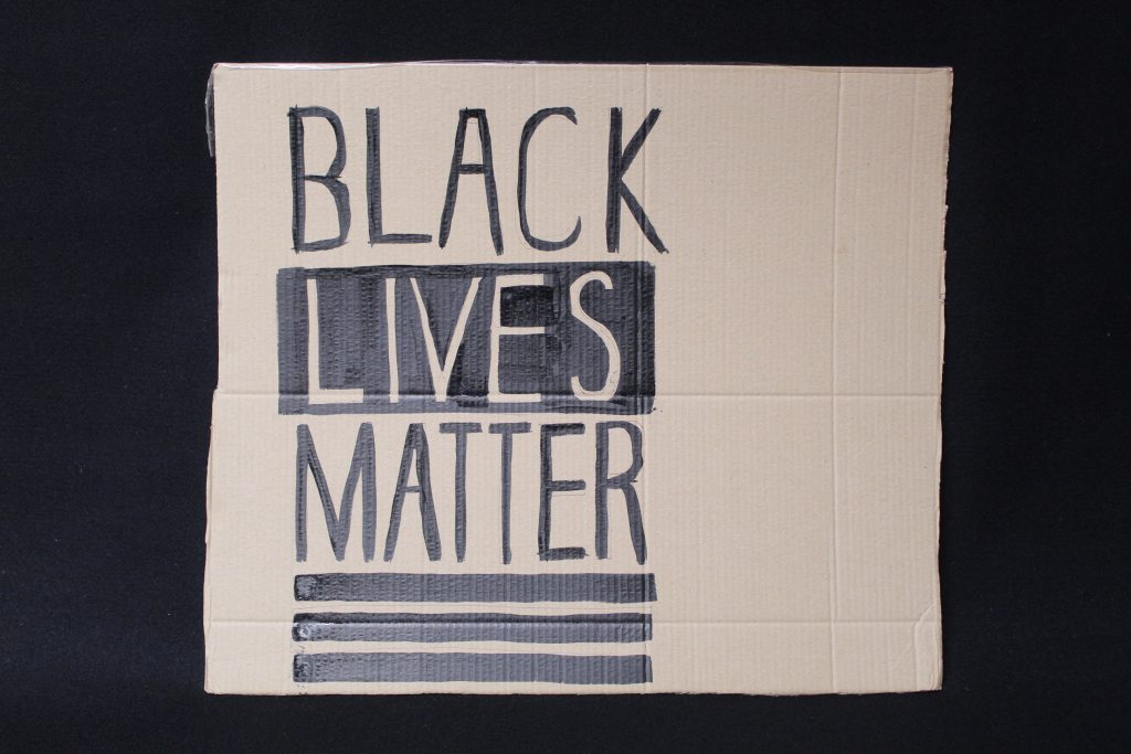 STOPM_2020_455b: Photo of a home made placard, on a black background. The sign has been made from a section of a cardboard box.  The sign has been drawn and painted with the words 'BLACK LIVES MATTER' in black paint