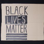 STOPM_2020_455b: Photo of a home made placard, on a black background. The sign has been made from a section of a cardboard box.  The sign has been drawn and painted with the words 'BLACK LIVES MATTER' in black paint Thumbnail