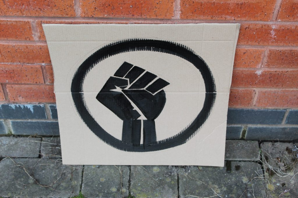 STOPM_2020_456a: Photo of a home made placard, stood in front of a red brick building. The sign has been made from a section of a cardboard box.  The sign has been painted with the symbol of a black raised fist in black paint.