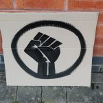 STOPM_2020_456a: Photo of a home made placard, stood in front of a red brick building. The sign has been made from a section of a cardboard box.  The sign has been painted with the symbol of a black raised fist in black paint. Thumbnail
