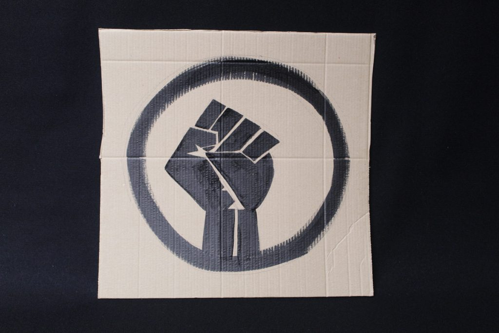 STOPM_2020_456b: Photo of a home made placard, on a black background. The sign has been made from a section of a cardboard box.  The sign has been painted with the symbol of a black raised fist in black paint.
