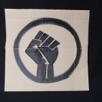 STOPM_2020_456b: Photo of a home made placard, on a black background. The sign has been made from a section of a cardboard box.  The sign has been painted with the symbol of a black raised fist in black paint. Thumbnail
