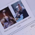 STOPM_2020_545d:  close-up view of a month in Valerie's Gallery calendar - the image on the left is a painting of Marie Antoinette, on the right is Valerie's version: wearing a costume dress and cutting a cake. Text says 'Marie Antoinette at the Guillotine, With Cake'. Thumbnail